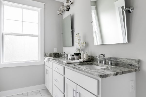 Dual vanity and white cabinetry in bathroom by Richmond Hill Design-Build