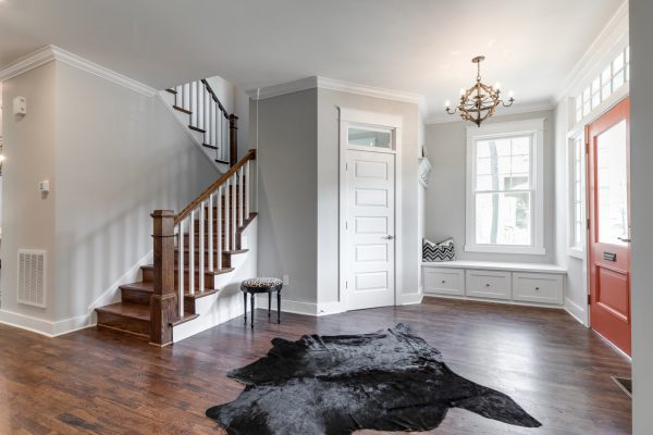 Foyer with stairwell in renovated home with open floor plan built by Richmond Hill Design-Build
