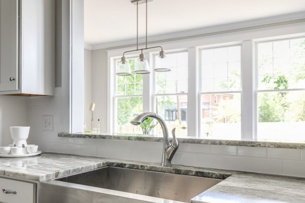 Kitchen with stainless farmhouse sink in renovated home built by Richmond Hill Design-Build