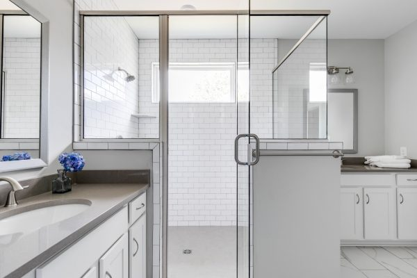 Corner shower with subway tile in owner's suite by Richmond Hill Design-Build