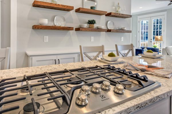 Gas cooktop and floating wood shelving in beautiful home by Richmond Hill Design-Build