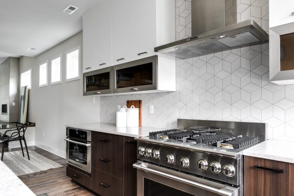 Stunning kitchen with stainless steel appliances in new contemporary home by Richmond Hill Design-Build