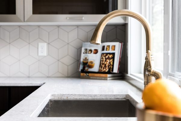Gorgeous kitchen with gold faucet in new contemporary home by Richmond Hill Design-Build