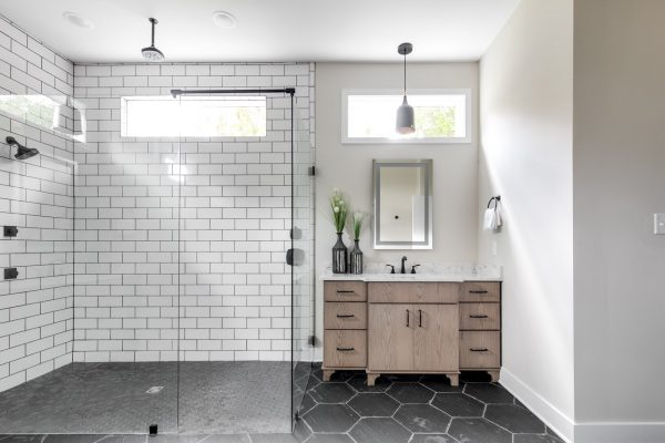 Gorgeous owner's bathroom with oversized shower and transom window in new contemporary home by Richmond Hill Design-Build