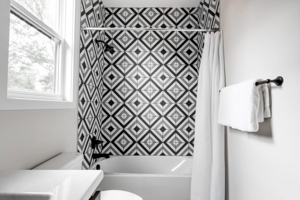 Guest bathroom with tile shower wall in new contemporary home by Richmond Hill Design-Build