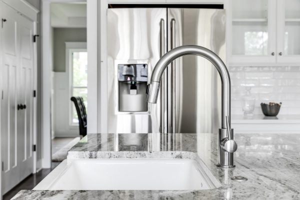 Farmhouse sink and chrome faucet in kitchen in home built by Richmond Hill Design-Build