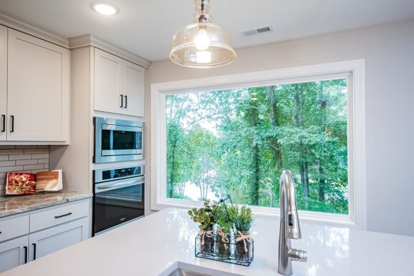 Huge, picture window in gorgeous kitchen with island in renovated ranch home on Lake Cherokee by Richmond Hill Design-Build