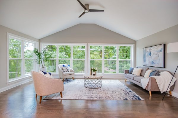 Family room with wall of windows overlooking lake in renovated ranch home by Richmond Hill Design-Build