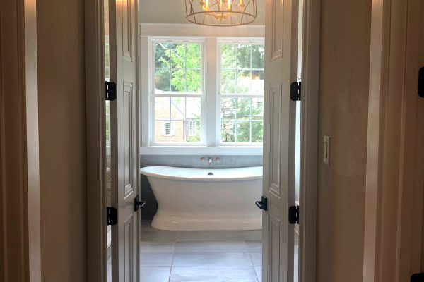Primary bedroom view into bath in new home built by Richmond Hill Design-Build
