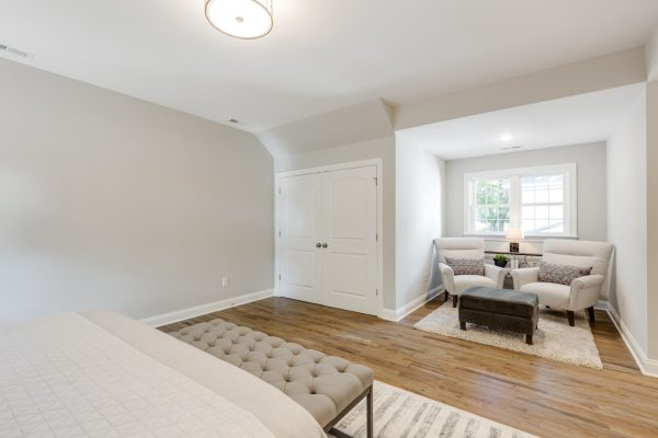 Owner's bedroom with sitting area in renovated home by Richmond Hill Design-Build